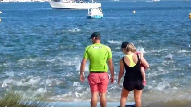 This couple stay ashore as flapping salmon turn Perth's Swan River into turmoil.