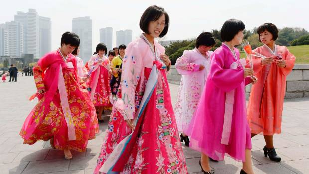 North Korean women wearing traditional costumes walk towards bronze statues at Mansudae in Pyongyang.