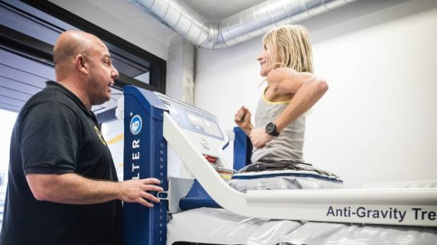 HealthFit director Theo Bostrovas helps Sarah Catherall run on the gym's new 'Anti-Gravity' treadmill.