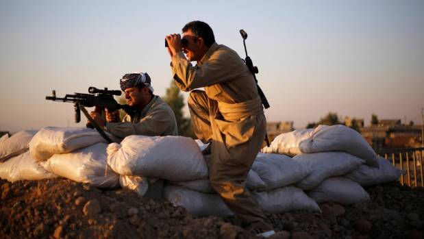 Kurdish Peshmerga fighters observe the front line with Islamic State in Northern Iraq.