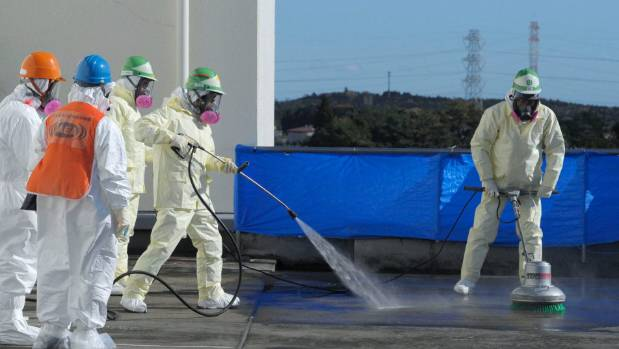 Workers decontaminate a building near the tsunami-crippled Fukushima Daiichi nuclear power plant in 2011. At the time, ...