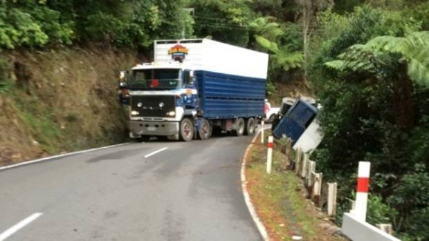 A cattle truck is blocking the road and a trailer is hanging over the edge of Blue Mountains Road in Upper Hutt.