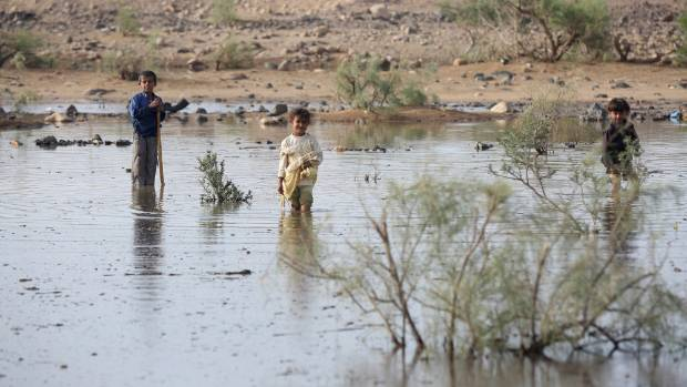 Children play in floodwater near a camp for internally displaced people in the Dhanah area of the central province of ...
