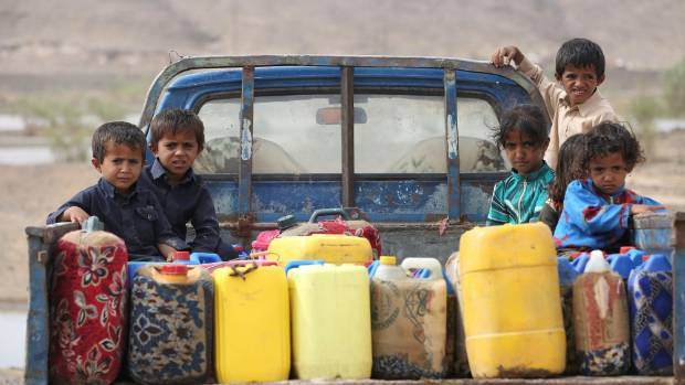 Children ride on the back of a truck loaded with water jerrycans at a camp for internally displaced people in the Dhanah ...