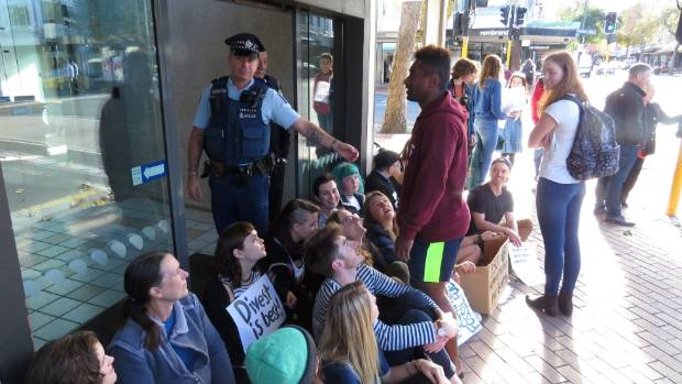 Protesters block the entrance a  branch of the ANZ in Dunedin.