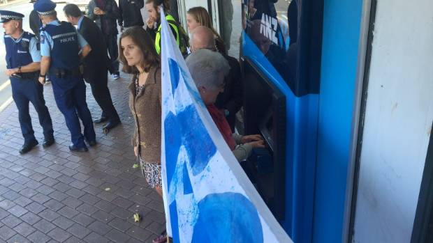 An elderly customer uses an ATM as activists protest outside a Dunedin branch of the ANZ.