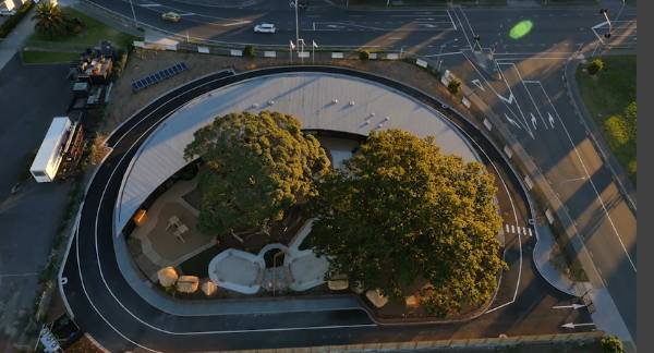 The cocooning shape can be seen from above - the centre wraps around two protected 100-year-old trees on the site - a ...