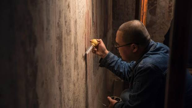 A technician working at the restoration of wall paintings in cave 98 of the Mogao grottoes.