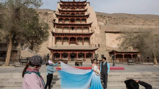 A couple poses during a wedding photo shoot in front of the nine-story tower built around cave 96, China.