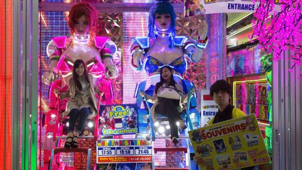 Women sit in 'robot chairs' outside the Robot Restaurant in the Shinjuku area of Tokyo, Japan.