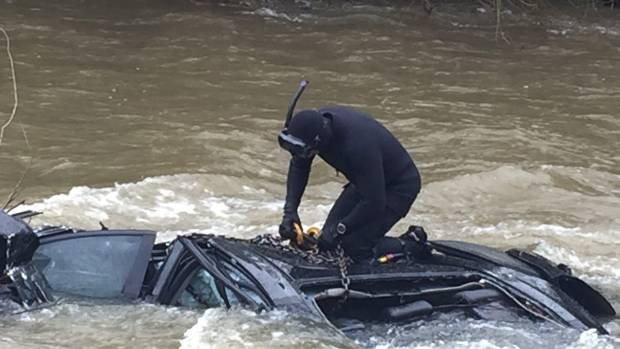 A members of the Police National Dive Squad works to retrieve the wreckage of a car.
