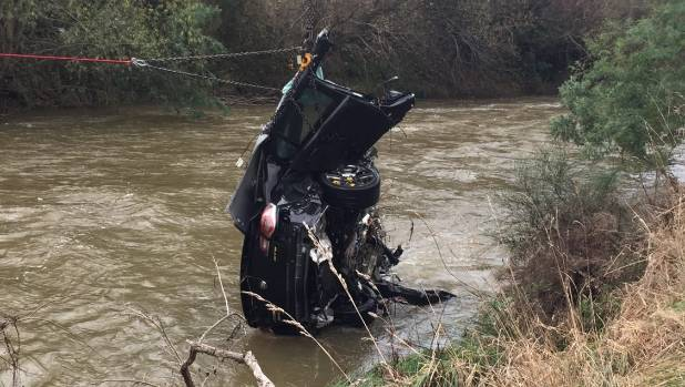 The wreckage of a car that crashed into the Waipoua River, near Masterton, is retrieved from the water.