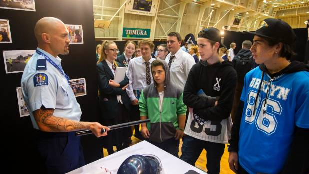 Constable Bob Katene, of Timaru, shows a police baton to YMCA students Quintin Miller, Dylan Hurst and Hamish Howell at ...