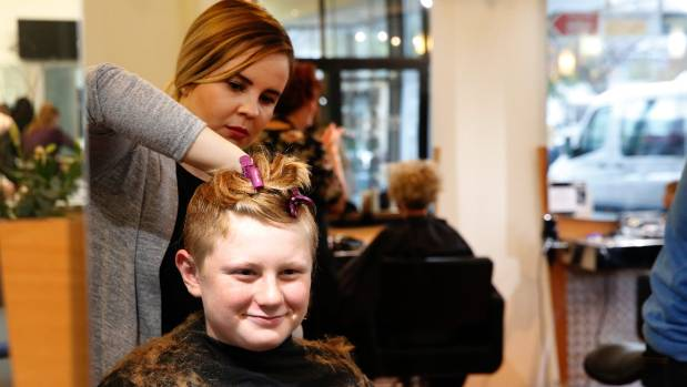 Aboki Hairdressers' Libby Ferguson gives Lake Rotoiti School student Charlie Younger, 11, a hair cut in a 1940's style ...