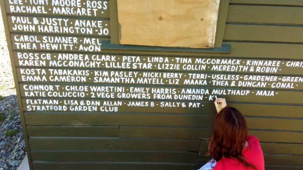 Painting the names of donors to the Otakaro Orchard on a shed at the site.