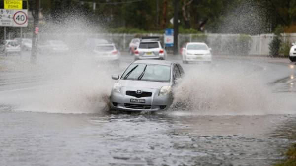 A car attempts to cross flooded road.