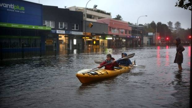 Kayakers float down the the road in Narrabeen, New South Wales.