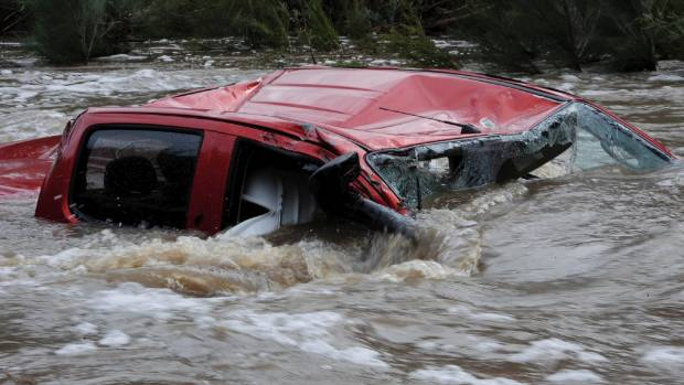 The driver of this ute died after trying to cross the raging torrent near Canberra during Sunday's constant rain across ...