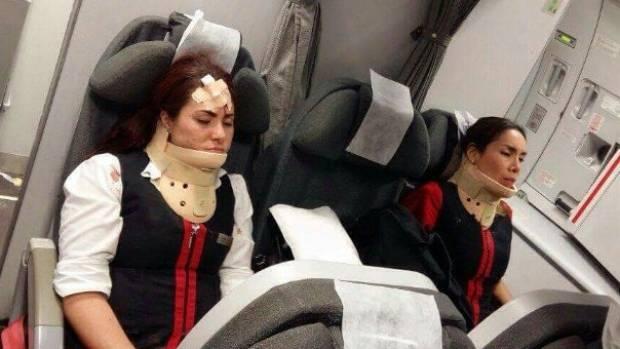 Flight attendants sit in neck braces on flight that injured 23.