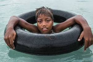 Tire, 10, uses a car tyre inner tube to swim in a flooded area of his home village of Eita. South Tarawa, Kiribati.