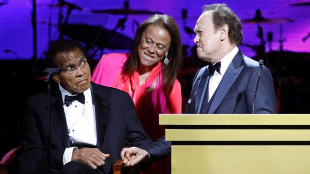 Billy Crystal (R) and Muhammed Ali (L) hold hands together with Lonnie Ali at the Muhammad Ali Celebrity Fight Night ...
