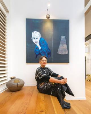 Anne on the upstairs landing, beside one of her own favourite paintings, The Masks We Wear.