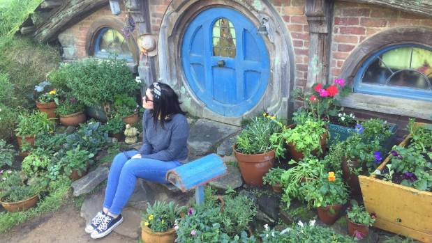 Hobbiton visitor Britt Mann poses for a photo outside a hobbit hole.