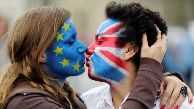 Two activists with the EU flag and Union Jack painted on their faces kiss in front of Brandenburg Gate to protest ...