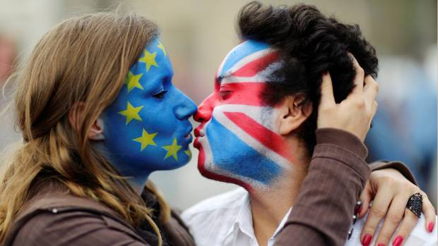 Two activists with the EU flag and Union Jack painted on their faces kiss each other in front of Brandenburg Gate to ...
