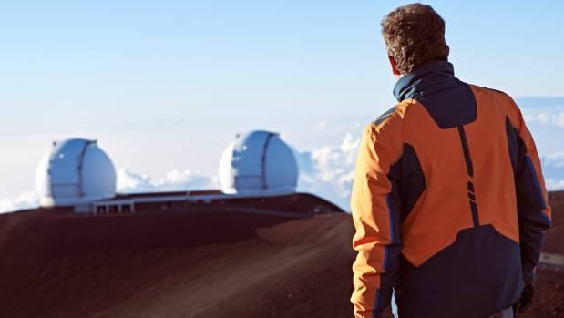 Matt Mountain standing on Mauna Kea in Hawaii facing the Keck Observatory.