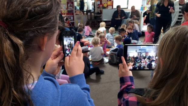 Ahuroa School pupils snap photos at Mahurangi Kindergarten's 'Grandparents and Special Person Day' lunch for their ...