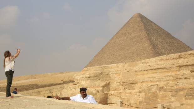 A policeman (R) stands guard as a touris takes a photo at the Giza Pyramids on the outskirts of Cairo, Egypt.