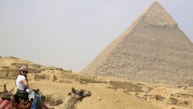 A British tourist rides a camel in front of the Giza pyramids.