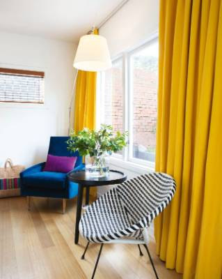 The yellow drapes in the kitchen are from James Dunlop Textiles; Nicole found the vintage black and white coolie chair ...