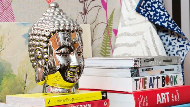 Behind the Buddha head in the office is a piece of fabric Nicole had framed.