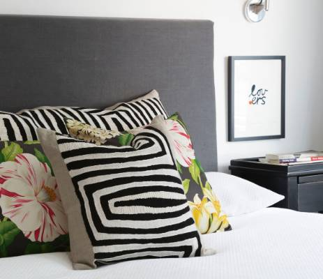 The cushions in the master bedroom are covered in Larsen and Sanderson fabrics, and the artwork is by Rachel Castle.