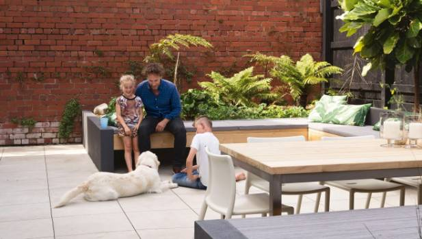 The family relaxes in the backyard; the table is Nicole's design, and is built from vitex timber that will naturally ...