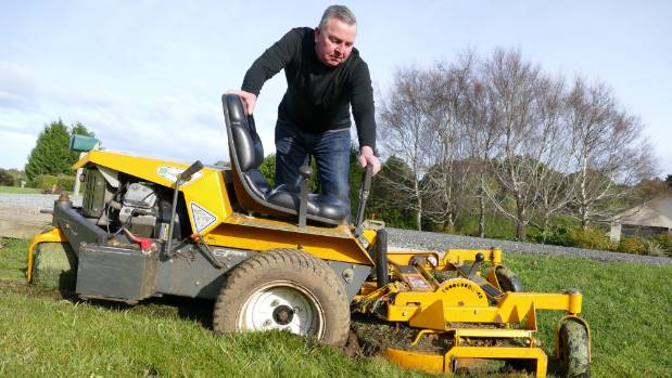 Otatara resident Brent Fraser with his bogged lawn mower which the council refused to tow out.