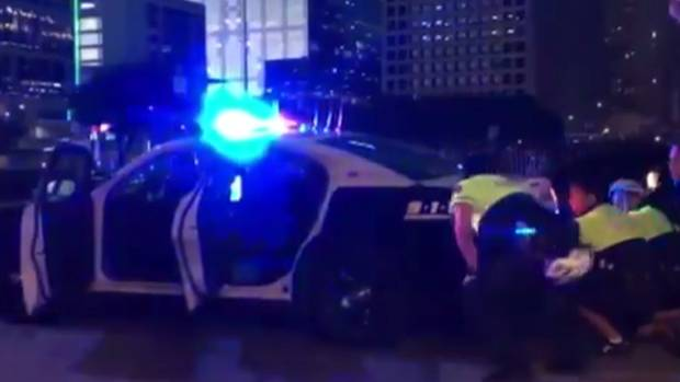 Police shelter behind a patrol car after snipers open fire in Dallas, Texas.
