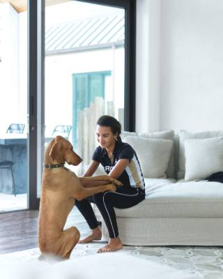 Christelle plays with the family dog Marley, a Hungarian vizsla.