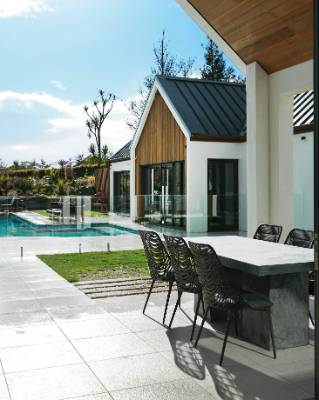 The Blanchards love entertaining around the pool, redesigned into a T shape; Morgan wicker dining chairs in Cocoa and ...