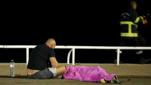 A man sits next to a body seen on the ground in Nice, France, when a truck ran into a crowd celebrating the Bastille Day ...