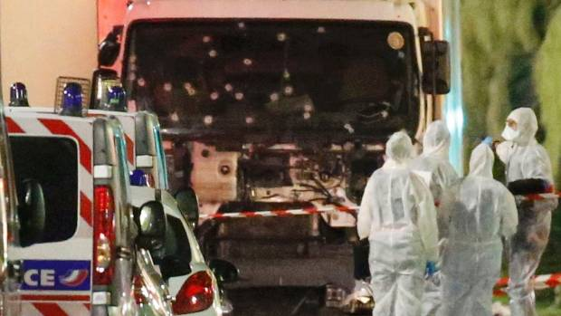 French police forces and forensic officers stand next to a truck that ran into a crowd celebrating the Bastille Day ...