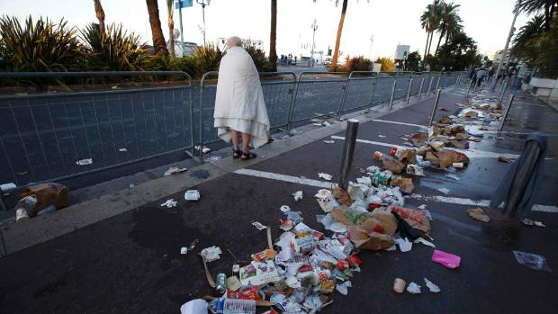 A man walks through debris on the sea front in Nice the morning after a lorry ploughed into pedestrians celebrating ...