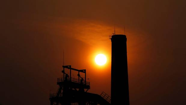 The sun sets behind a chimney of a steel mill in Tangshan, Hebei province.