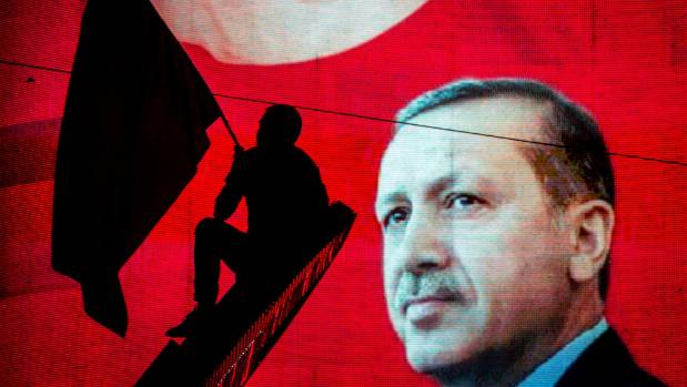 A supporter of Turkish President Recep Tayyip Erdogan waves a flag against an electronic billboard during a rally in ...