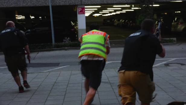 Police officers rush to the Olympia Einkaufzentrum mall after gunmen opened fire.