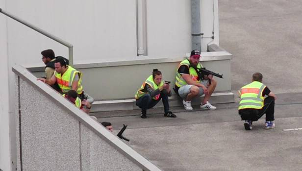 Police with automatic weapons group on the roof of the Olympia mall after the shootings.