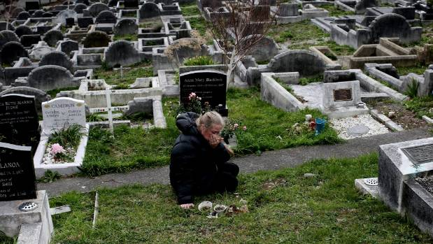 Tracy Murphy grieves at the unmarked grave site of Anaru Rogers, her step brother who was killed by his biological ...