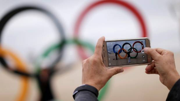 A woman takes pictures with a mobile phone in front of the Olympic rings placed at the Copacabana beach in Rio de ...